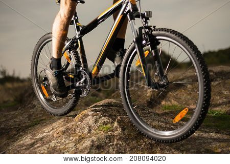 Close up Photo of Cyclist Riding the Bike Down the Rock. Extreme Sport and Enduro Biking Concept.