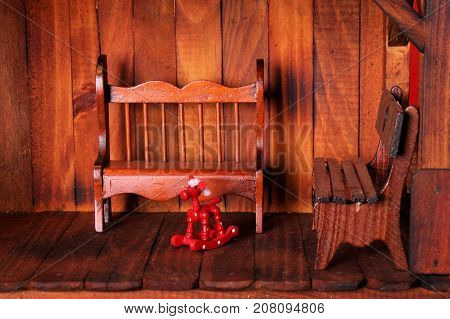 Front porch in miniature showing benches and tiny wooden rocking horse.