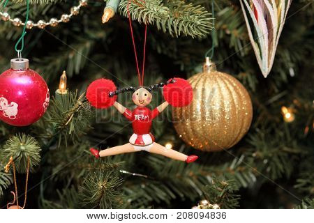 Wooden Christmas tree ornament of a cheerleader hanging on the tree.