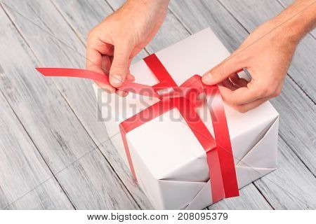 Hands tie a ribbon on a white gift box, on a wooden gray background. View from above.