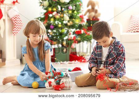 Cute children making Christmas handicrafts on floor
