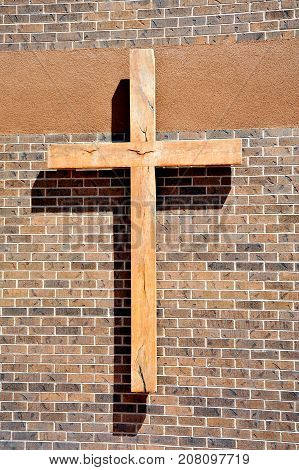 Wooden cross on the wall of a place of worship.