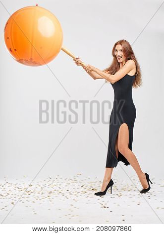 Celebrating young woman in a Halloween dress kicking an orange pumpkin pinata balloon with a ball on a light gray background.