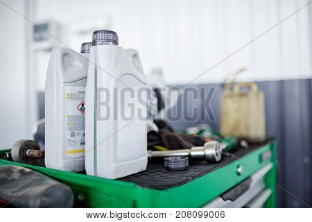 Machine oil in a white container on a green box with tools close-up