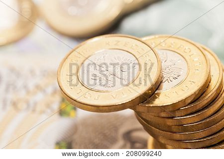 Polish banknotes and coins photographed close-up. Shown details of money with international designation - PLN. Shallow depth of field, photo taken from above