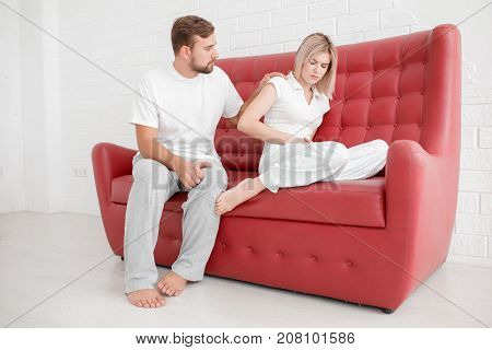 Young man with a beard and supports a beautiful girl in white when it hurts against a white background