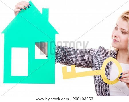 Ownership property concept.. Human hands holding green paper house model with key cutout. New flat apartment. Isolated on white