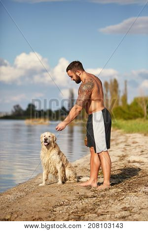 Beautiful golden retriver and owner playing on the beach and having fun. Cutie pet and man enjoying life on the fresh air on the water background. Full lenght of man.