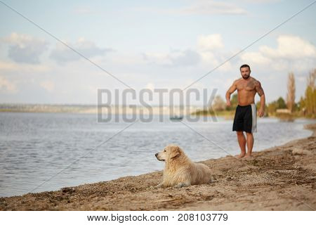 Beautiful golden retriver and owner playing near the river and having fun. Cutie pet and man enjoying life on the fresh air on the water background. Full lenght of man.