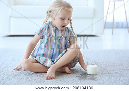 Cute little girl with glass of milk sitting on carpet near wet spot