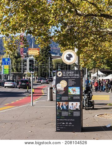 Zurich, Switzerland - 7 October, 2017: advertising pillar with playbill of the Zurich Film Festival, people and traffic on General Guisan quay. Zurich is the largest city in Switzerland and the capital of the Swiss canton of Zurich.