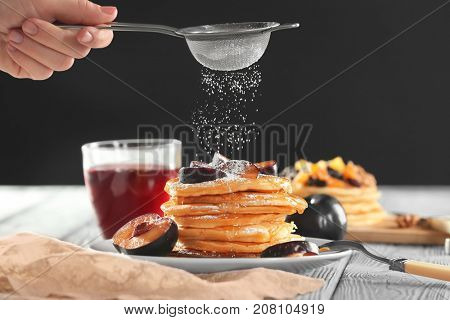 Woman decorating tasty pancakes with powdered sugar on table