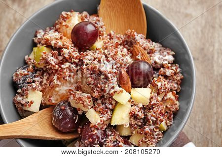 Mixing quinoa salad on wooden background