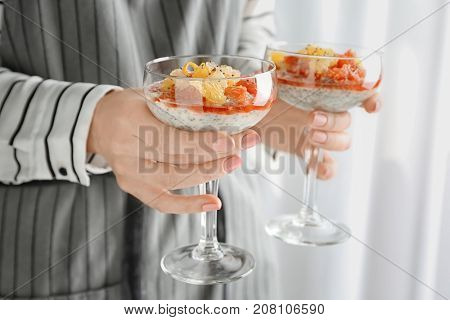 Woman holding glasses with delicious chia seed pudding on blurred background