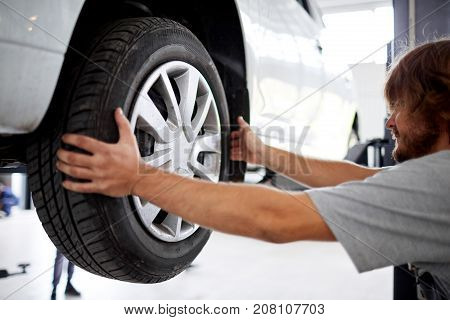 Auto mechanic checking the suspension or brakes in the car on a lift in a car workshop