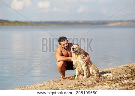 A young, handsome man without a shirt praises his dog after playing on the water