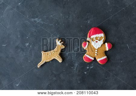Ginger men with colored glaze on a gray background .. Gingerbread. Christmas cookies. Ginger man in a colored sweater. Gingerbread Santa