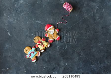 Ginger men with colored glaze on a gray background .. Gingerbread. Christmas cookies. Ginger man in a colored sweater