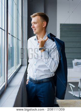 Portrait of a sccessfull and confident young director in a classy dark blue formalwear and white shirt on a blurred office background.