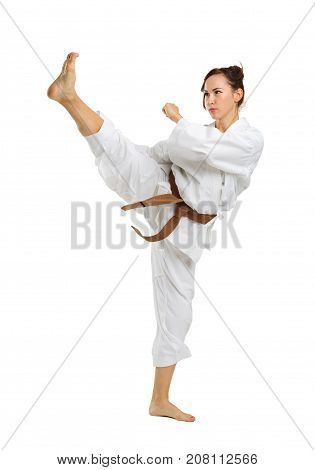 A girl in white uniform for karate with a brown belt on an isolated white background executes kicks with legs