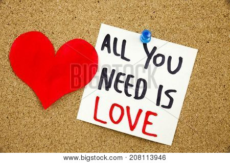 A Yellow Sticky Note Writing, Caption, Inscription Phrase All You Need Is Love In Black Ext On A Sti