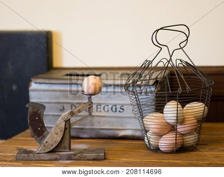 A vintage measuring device to grade eggs and a wire basket with eggs awaiting measurement.