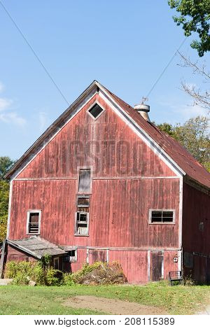 Rustic old red barn in disrepair with grass in the foreground and blue sky above. A weathervane sits on the roof of the barn.