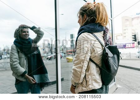 girl in autumn clothes looks at her reflection in the glass and smiles