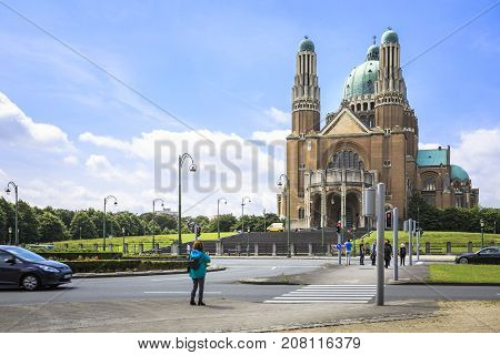 BRUSSELS BELGIUM - JUNE 19 2016: Picture of the Basilica of the Sacred Heart in Koekelberg from across the street with tourists and cars in a sunny day with clouds. Brussels Belgium.