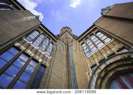 BRUSSELS BELGIUM - JUNE 19 2016: Detail of the facade of the Basilica of the Sacred Heart in Koekelberg with big windows with sky reflection in a sunny day with clouds. Brussels Belgium.