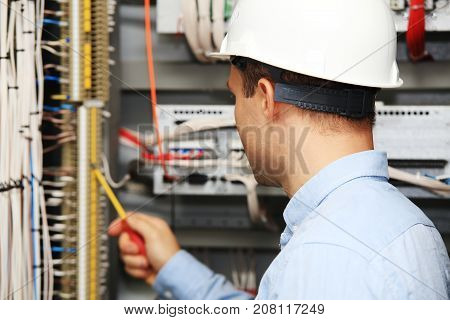 Engineer with screwdriver checking wire connections. Young electrician at work.