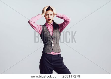 beautiful girl in a cute pink shirt is holding her head and looking at the camera