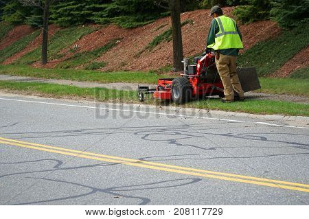outdoor worker working on mowing the lawn near the street