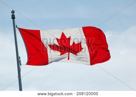 Canadian flag blowing in the wind on a cloudy evening