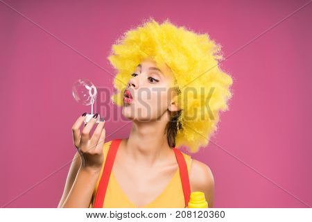 girl in a clown suit blows soap bubbles on a pink background