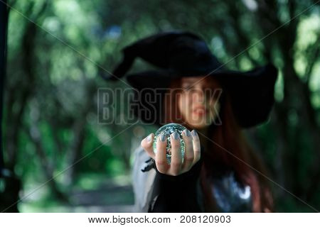 Photo of witch stretching hand with ball