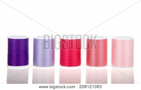 Five spools of thread isolated on white sitting on a reflective surface lined up in a row.
