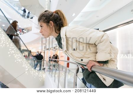 girl in autumn clothes peeking behind the railing in a shopping center