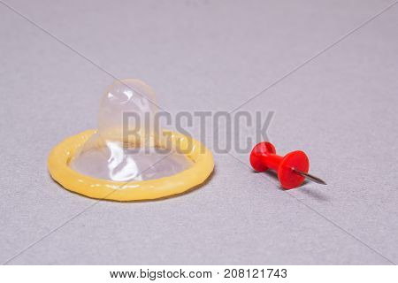 Condom and office pin on a gray background. Broken pierced condom