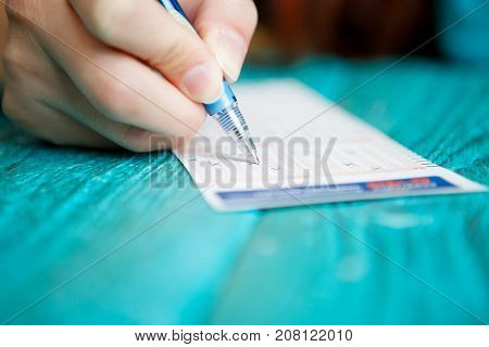 Photo of man's hand with pen and lottery ticket