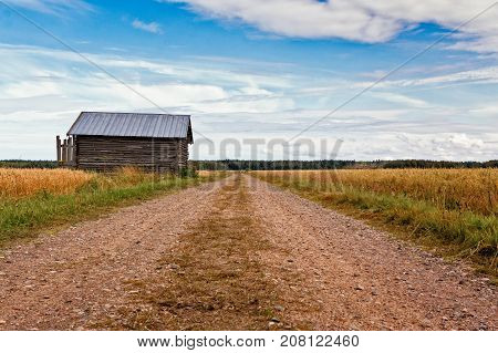 An old barn house stands by the gravel road leading through the fields in the rural Finland.