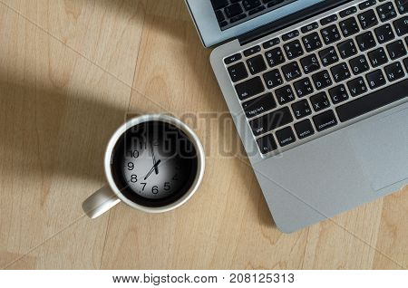 Top view of Laptop notepad and coffee cup which shown time over surface wooden backgroundflat lay