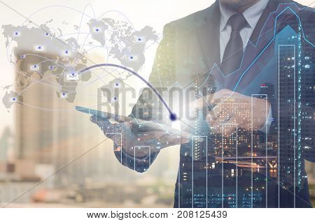 Double exposure of businessman using tablet for sending the email with cityscape and financial graph on blurred building background Business Trading concept Elements of this image furnished, 3D