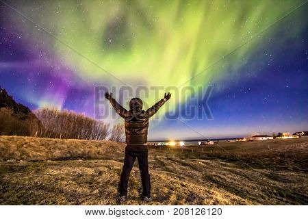 Aurora borealis or the northern lights with back side of traveller man in action show arms with motion hand Iceland april 2016