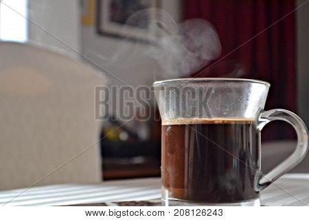 Cup of black coffee whit heart shaped foam