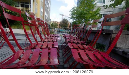 Row Of Red Metal Chairs In Empty Urban Park