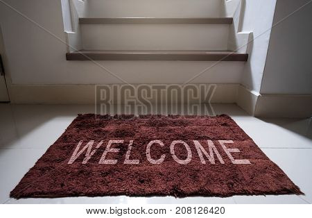 Welcome doormat on white floor with step to second floor, home interior household