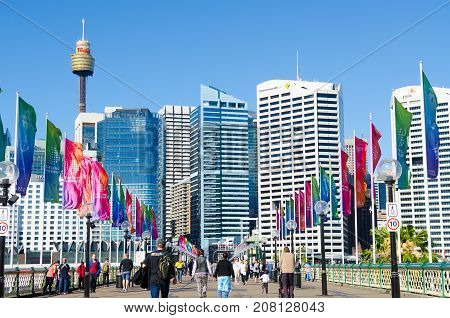 SYDNEY - AUGUST 16 2017:People crossing the Pyrmont Bridge at sunset in Darling Harbour a recreational and pedestrian precinct western to Sydney central business district in New South Wales Australia