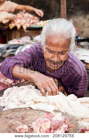 Yangon Burma - 2016 December 22 : An old female meat vendor on a street market in downtown Yangon with intestines and a chopping block