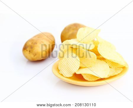 Potato chips on wooden plate over white background.